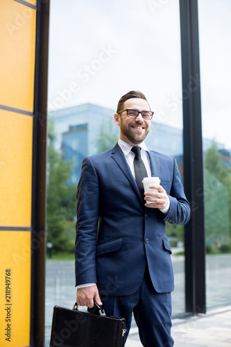Fototapety, obrazy: Young male in business dress, eyeglasses keeping plastic cup, looking at camera and standing near windows