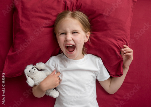 Valokuva  Child girl lying on the bed refuses to sleep