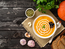 Funny Food For Halloween. Pumpkin Puree Soup, Spider Web, Dark Old Wooden Table, Top View, Copy Space