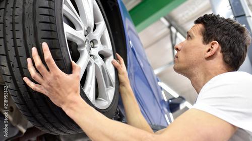Valokuva Reifenwechsel in einer autowerkstatt // tyre change in a car repair shop - worke