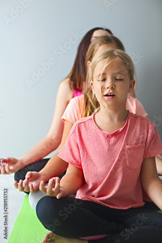 Young woman having fun with kids doing yoga - Buy this stock