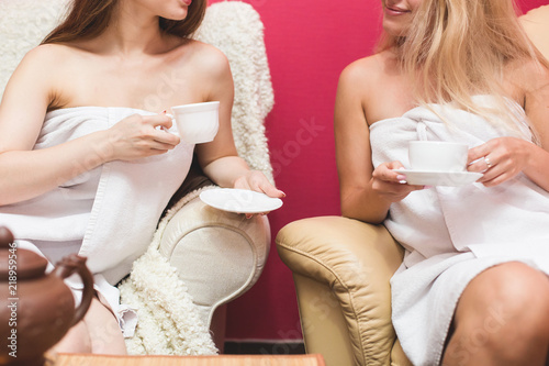 Fototapeta Three young cute girls in white bathrobes are drinking tea in the spa salon. Rest after sauna and beauty salon procedures obraz na płótnie