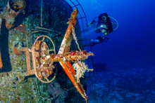 SCUBA Divers Exploring A Large Underwater Shipwreck Near A Tropical Coral Reef