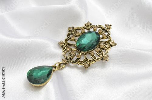 golden vintage brooch with emeralds on silk Fototapete