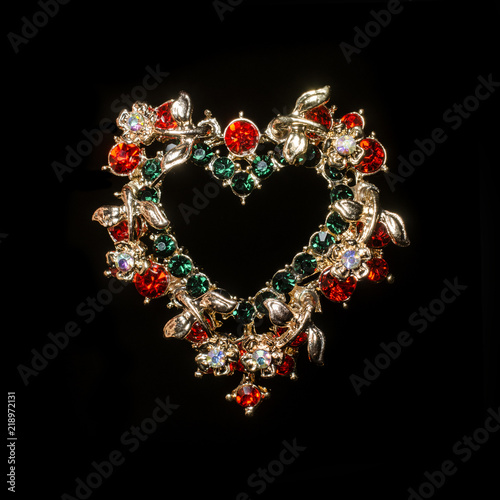Fotografija gold brooch heart with diamonds isolated on black
