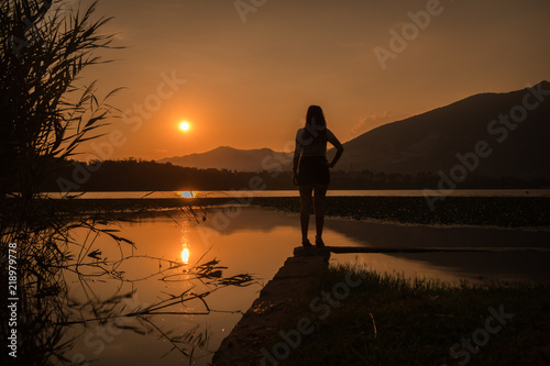 Fotografía  girl silhouette standing over the lake annone brianza lecco italy