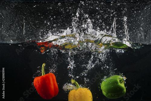 Printed kitchen splashbacks Splashing water several coloured paprika falling into water splash with many bubble