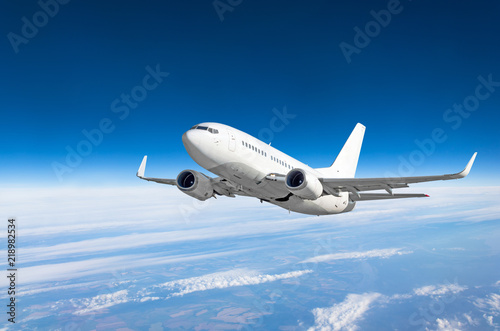 Passenger airplane fly on a hight above clouds and blue sky.