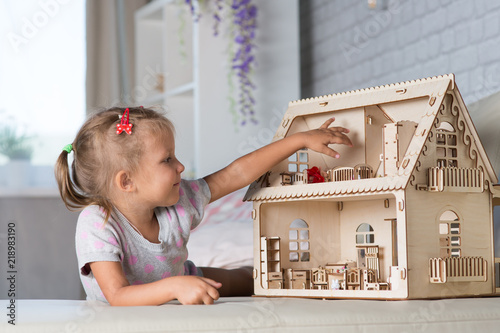 Fototapeta a girl playing with a dollhouse