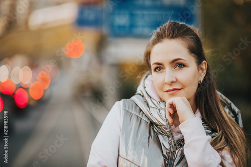 Photographie  Outdoor portrait of young woman posing on the city street, wearing silver jacket