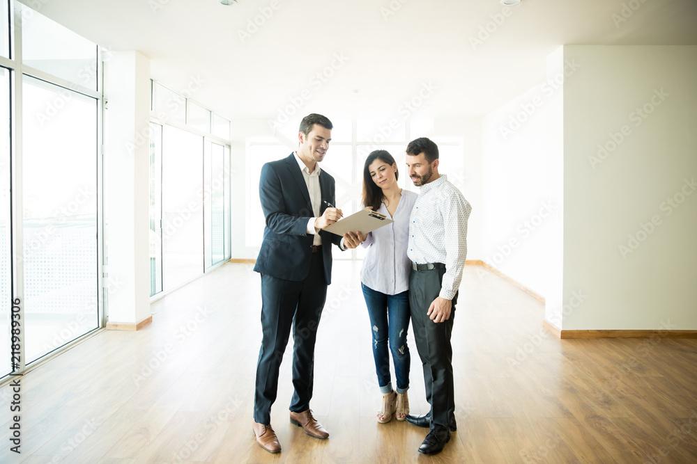 Fototapeta Realtor Explaining Agreement To Couple In New Apartment
