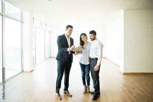 Photo Realtor Explaining Agreement To Couple In New Apartment