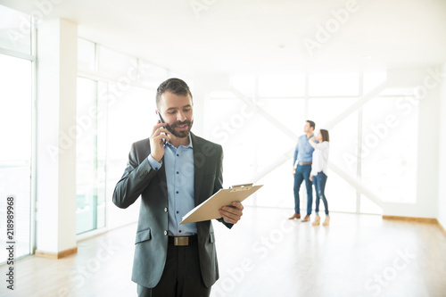 Fotografia Real Estate Agent Using Mobile Phone At New Home