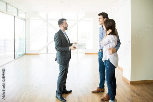 Fotografía  Broker Discussing With Couple While Standing In New House