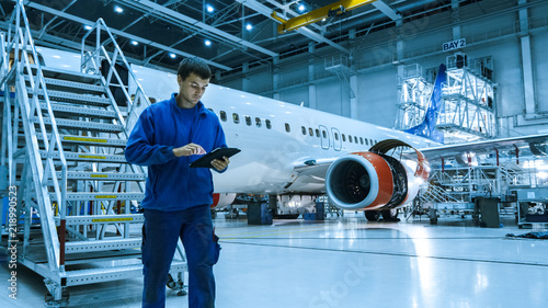 Fototapeta Aircraft maintenance mechanic in blue uniform is going down the stairs while using tablet in a hangar. obraz