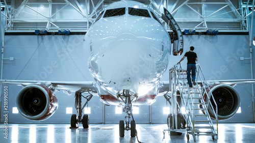 Stampa su Tela Brand New Airplane Standing in a Aircraft Maintenance Hangar while Aircraft Maintenance Engineer/ Technician/ Mechanic goes inside Cabin via Ladder/ Ramp