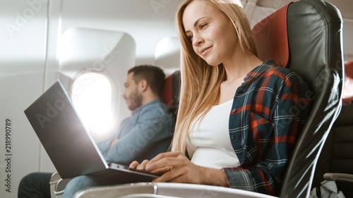 On Board Of Commercial Airplane Beautiful Young Blonde Works On A Laptop While Her Hispanic Male