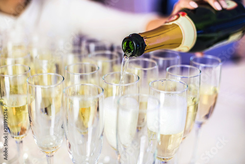 Pouring champagne into wine glasses. Champagne flutes on a wedding or new year eve party