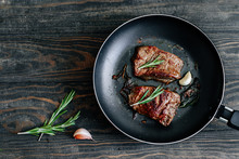 Roast Beef Steak With Rosemary And Garlic In A Frying Pan On A Wooden Table Top View