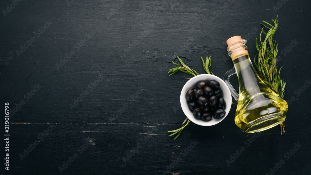 Fototapety, obrazy: A set of olives and olive oil and rosemary. Green olives and black olives. On a black wooden background. Free space for text.