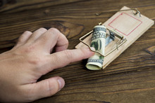 A Man's Hand Got Caught In A Mousetrap With Bait Money Dollar Bills. Concept Business Risk, Pimat The Attacker, Bribe.