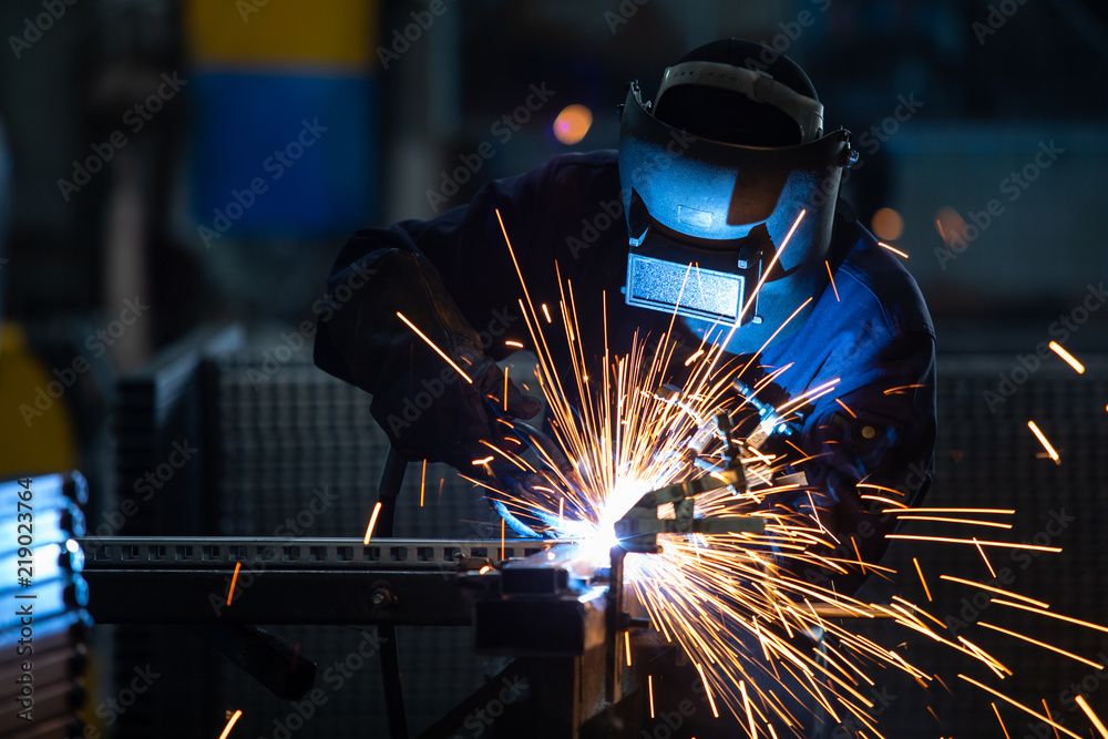 Fototapety, obrazy: Workers wearing industrial uniforms and Welded Iron Mask at Steel welding plants, industrial safety first concept.