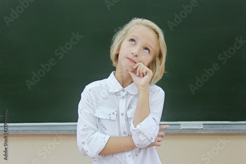 Adorable blond kid girl thoughtful in a classroom near a chalkboard Wallpaper Mural
