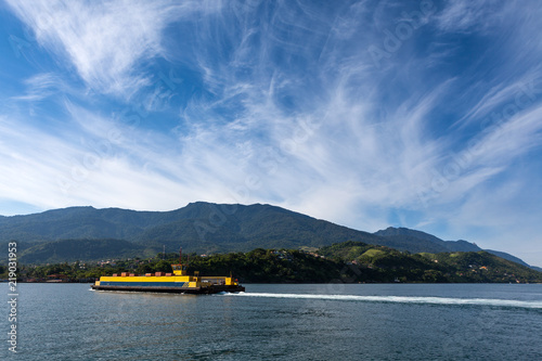 Fotografía  Panoramic view with a ferryboat crossing the sea with mountain and blue sky on sunny summer day in Ilha Bela on the coast of São Paulo, Brazil