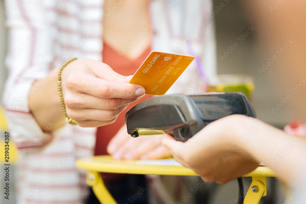 Fototapeta Gold card. Visitor of a cafe giving a gold card while a waitress holding a terminal