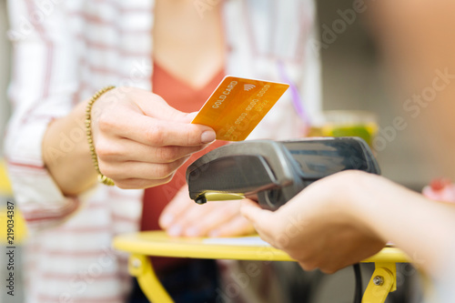 Gold card. Visitor of a cafe giving a gold card while a waitress holding a terminal