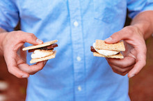 A Man In A Blue Shirt Holds Two Smores