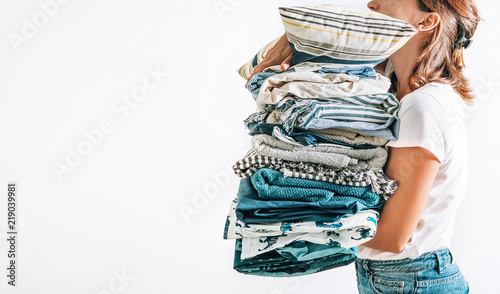 Fotografie, Obraz  Woman takes in hands big pile blue and beige blankets, towels and other home tex