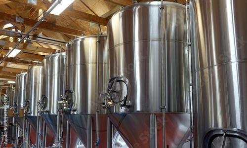 Vászonkép  Row of shiny metal micro brewery tanks.