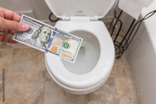 Fototapeta Holding crisp one hundred dollar bill into toilet; clena and bright; finance concept obraz na płótnie