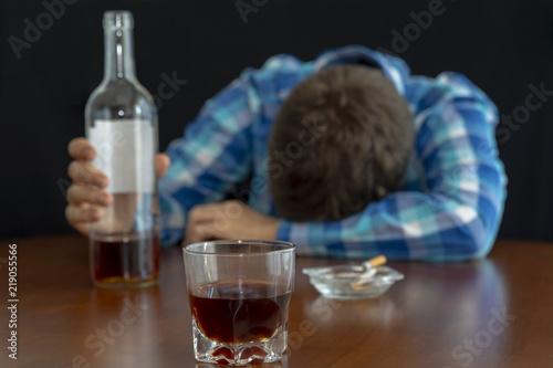 Fényképezés  Hombre borracho inconsciente con un vaso de bebida en la barra con un cigarro, p