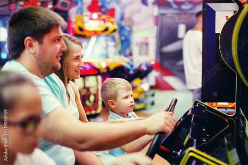 Cute girl plays a rifle shoots arcade in game machine at an amusement park Fototapet