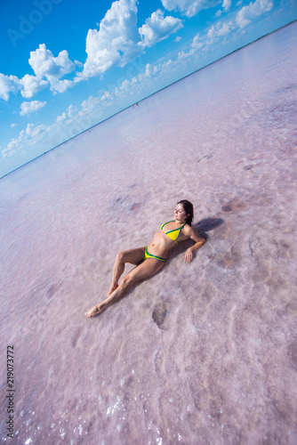 Poster Superheroes A girl in a yellow bikini is lying on her back in a pink salt lake. the bottom of the lake is covered with salt. the lake is pink because of the red algae. The girl lies on her back, leaning on her el