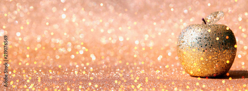 Rosh hashanah (jewish New Year holiday) concept. Traditional symbol, decorative glitter gold apple.