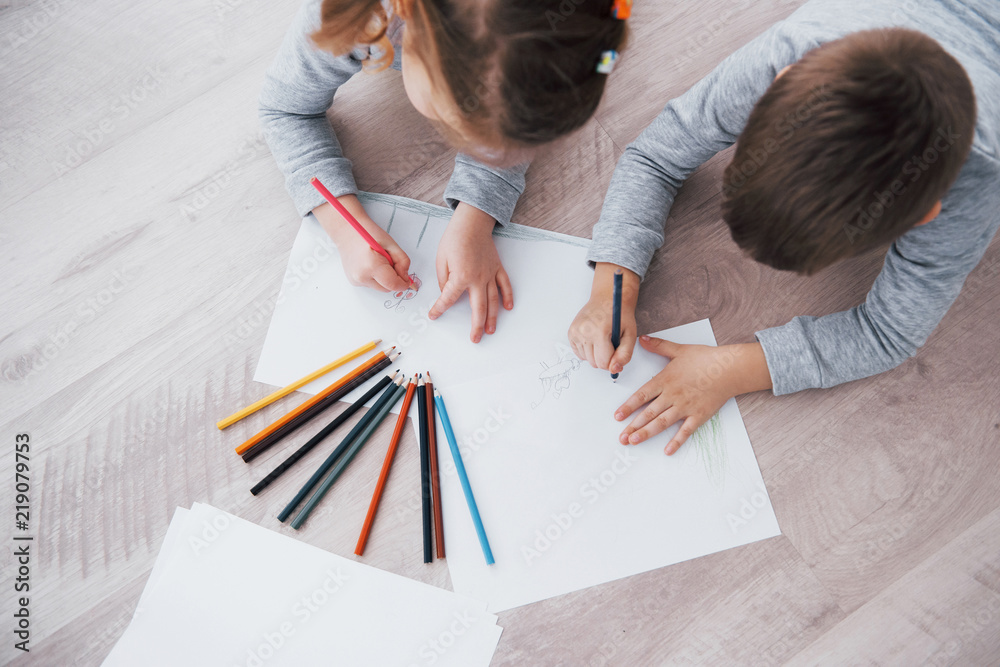 Fototapeta Children lie on the floor in pajamas and draw with pencils. Cute child painting by pencils