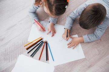 Djeca leže na podu u pidžami i crtaju olovkama. Slatko dijete koje slika olovke