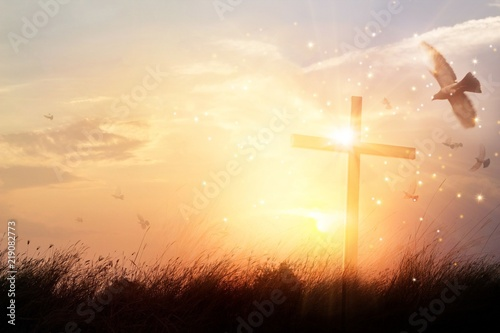 Silhouette christian cross on grass in sunrise background
