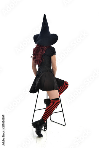 full length portrait of red haired girl wearing long black cloak, pointy hat and witch costume. seated pose on chair, isolated on white studio background.