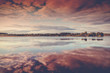Beautiful pink sunset on the lake, clouds reflected in the water, beautiful autumn landscape