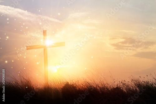 Silhouette christianity cross on grass field in sunrise background Fototapete