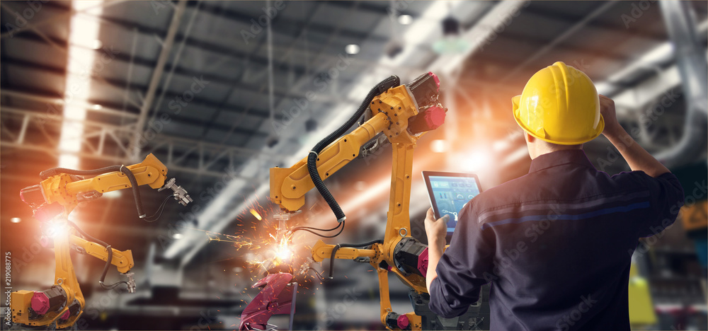 Fototapeta Engineer using tablet check and control automation robot arms machine in intelligent factory industrial on monitoring system software. Welding robotics and digital manufacturing operation.