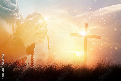 Canvas Print - Double exposure. Woman with cross praying on nature sunset background, hope concept