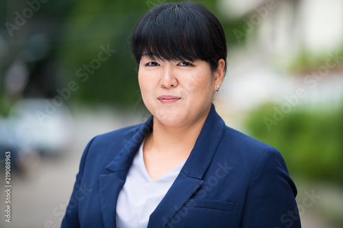 Fotografiet  Portrait of beautiful overweight Asian businesswoman outdoors
