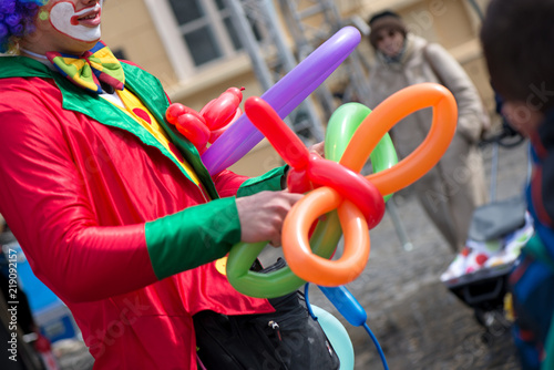 A freelance clown creating balloon animals and different shapes at outdoor festival in city center. School bag, angel wings, butterflies and dogs made of balloons. Concept of entertainment, birthdays