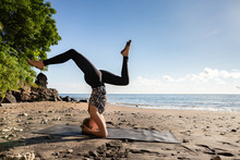 Young Woman In Black Doing Her Yoga On Asian Sand Beach.