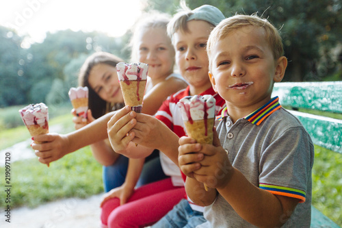 Valokuva  Group of four happy children eating ice cream together outdoor